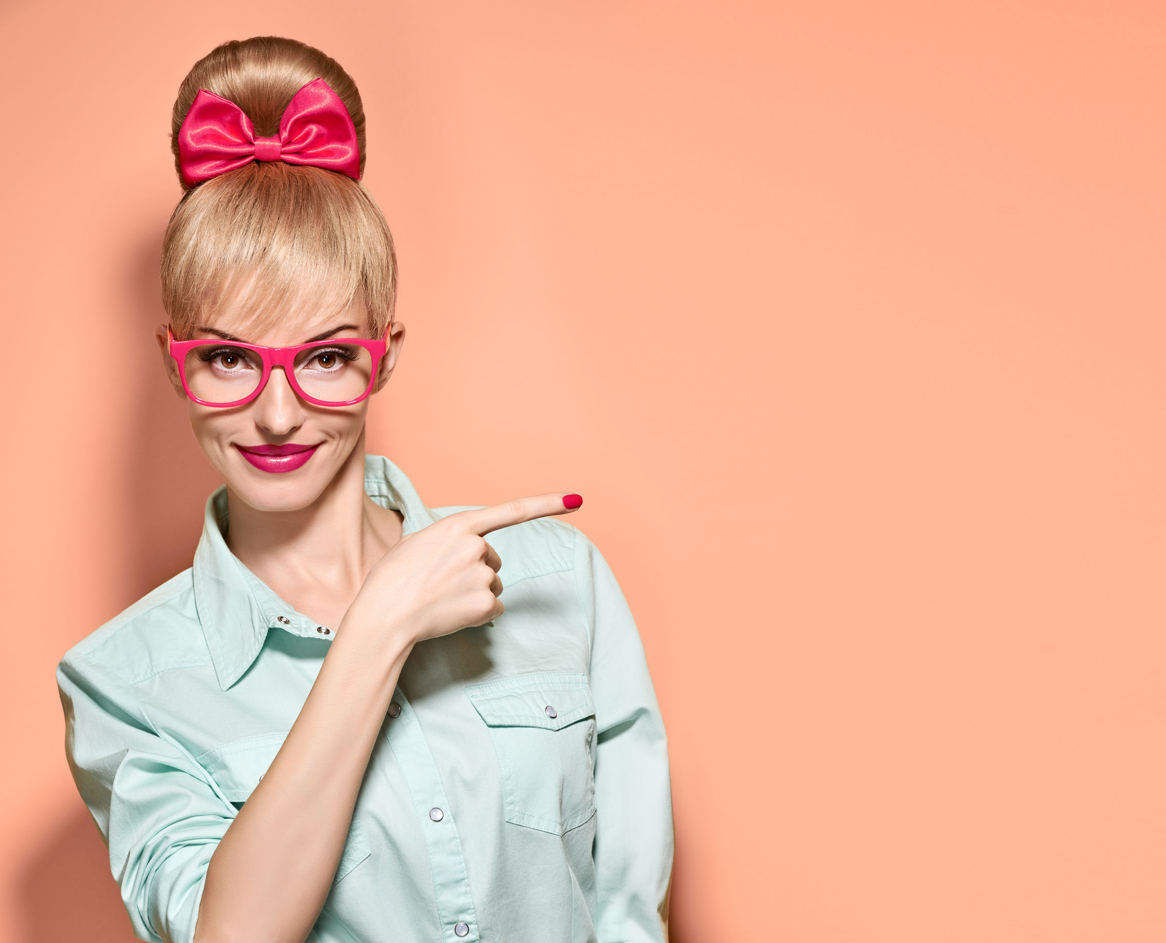 54853441 - beauty fashion woman in stylish glasses shows finger. attractive happy blonde hipster girl smiling, emotional. confidence, success, pinup hairstyle. unusual playful, expression nerd. vintageon pink